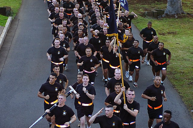 """A formation of Soldiers sprint toward the finishing mark as their commander renders honors at the conclusion of the 25th Infantry Division's 2010 division run, at Schofield Barracks, Hawaii, Jan. 29. This year's run marks the first occasion in which the division has been able to participate in a group event with the majority of """"Tropic Lightning's"""" brigades and battalions (U.S. Army photo by Spc. Jesus J. Aranda, 25th Infantry Division Public Affairs Office)."""