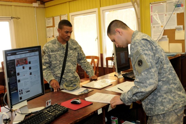 Spc. Steven M. Buck, a budget analyst with the 368th Finance Management Company, 36th Sustainment Brigade, 13th Sustainment Command (Expeditionary), assists Sgt. Rojan C. Woolridge, a human resources noncommissioned officer for the 3rd Battalion, 58th Aviation Regiment, do the distribution of finance for his unit Jan. 27, at Contingency Operating Location Basra, Iraq.