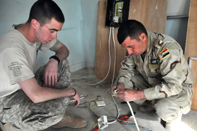 BAGHDAD -- Cpl. Adnan Muhammad Hassan, a 9th Iraqi Army Field Regiment soldier, gets some one-on-one instruction on wiring an electrical outlet box, during a 40-hour class taught by Spc. Danny Rockett, 101st Eng. Bn., at Joint Service Staion Al-Rasheed.  (U.S. Army photo by Sgt. Tracy Knowles, 101st Eng. Bn., USD-C)