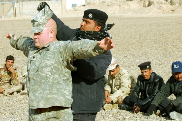 Muhammad Siad, an Iraqi Policeman, leaves no stone, or hat for that matter, unturned as he searches Spc. Anthony Pariseau, an infantryman with Company B, 4th Battalion, 9th Infantry Regiment, for hidden weapons during polling-station security training.