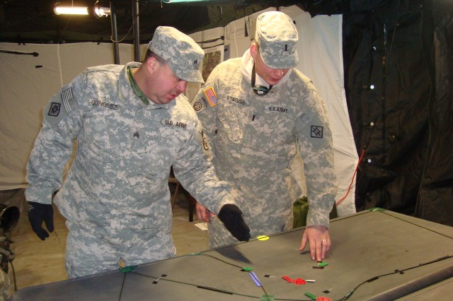 Sgt. Brian Quinonez, a team leader for the 18th Engineer Brigade's Personal Security Detachment, and 1st Lt. George Staggs, the executive officer for HHC, 18th Eng. Bde., use a sand table to discuss the next training mission. During a four-day training exercise in Mannheim, Germany, Soldiers from the PSD further developed their basic dismounted battle drills while being subjected to harsh winter weather.