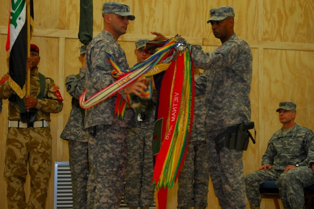 Maj. Gen. Vincent Brooks, 1st Infantry Division commander, and Command Sgt. Maj. Jim Champagne, 1st Inf. Div. command sergeant major, unfurl the 1st Inf. Div. colors during the transfer of authority ceremony at Contingency Operating Base Basra, Feb. 2, 2010.