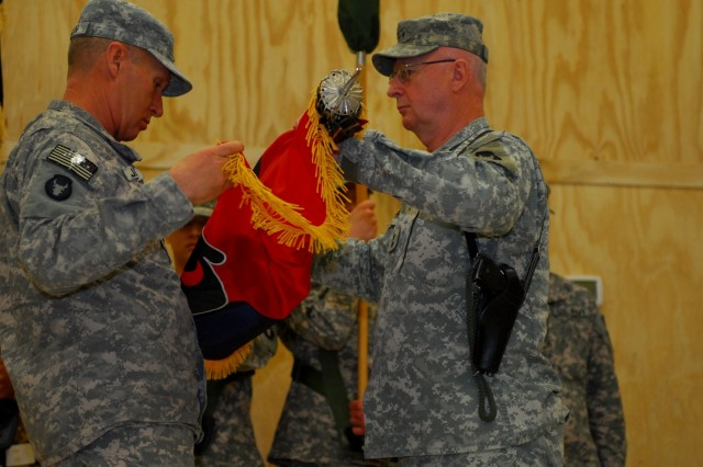 """Maj. Gen. Rick Nash, 34th Infantry Division commander, and Command Sgt. Maj. Doug Julin, 34th Inf. Div. command sergeant major, retire the """"Red Bull's"""" colors during the transfer of authority ceremony at Contingency Operating Base Basra,"""