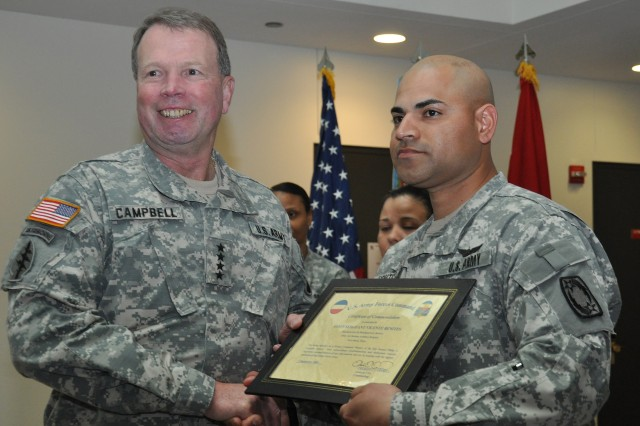 Gen. Charles Campbell, the commander of U.S. Army Forces Command, presents a plaque to Staff Sgt. Vicente Benites, a food service operations sergeant with the 69th Air Defense Artillery Brigade, at III Corps' headquarters building Tuesday for the recent accomplishments of the brigade's seven-man culinary team, which took top honors at FORSCOM level for excellence in food service in October 2009. Benites served as the team's lead sergeant.