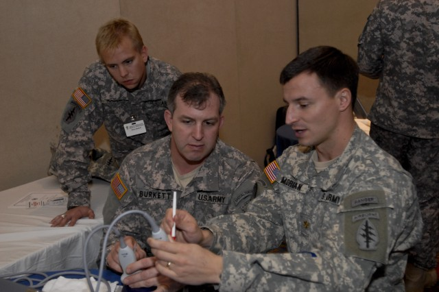Maj. Andrew Morgan (right), battalion surgeon, 1st Battalion, 3rd Special Forces Group (Airborne), explains some of the functions of a portable ultrasound machine to Sgt. 1st Class Kevin Burkett, a medic in the battalion, while Sgt. 1st Class Steven Radloff, also a medic in the unit, looks on during the Special Operations Medical Association's annual conference Dec. 15, in Tampa, Fla. Morgan and his office have been pushing to get more portable ultrasound machines, as well as practical training, in the hands of Special Forces medics in order to help empower them on the battlefield.