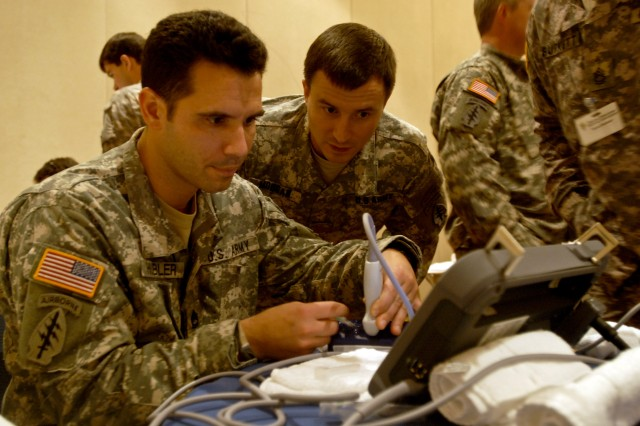 Sgt. 1st Class David Hubler (left), the senior medic with 1st Battalion, 3rd Special Group (Airborne), practices placing a syringe in a vein on a training device while Maj. Andrew Morgan, battalion surgeon, looks on during the Special Operations Medical Association's annual conference Dec. 15, in Tampa, Fla.