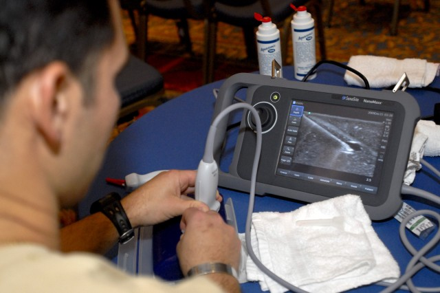 Sgt. 1st Class David Hubler, the senior medic with 1st Battalion, 3rd Special Group (Airborne), practices placing a syringe in a vein on a training device while using a portable ultrasound machine for guidance during the Special Operations Medical Association's annual conference Dec. 15, in Tampa, Fla. Ultrasound can see patient's veins as well as a syringe entering an area, which helps ensure the needle is put in the right place.