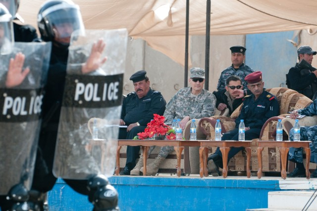 "Brig. Gen. Kenneth Tovo, deputy commanding general-west with U.S. DivisionAca,!""Center and Maj. Gen. Baha Husayn Abd Hassan, Al Anbar provincial director of police, watch policemen demonstrate their new skills at the Ramadi Training Center Jan. 28."