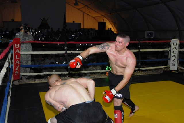Air Force Staff Sgt. Dominic Buzzeli,732nd Provost Marshal Office, throws a punch at his opponent, Sgt. James Barrett, 4th Brigade Combat Team, 1st Armored Division, during Friday Night Fights on Contingency Operating Base Adder, Iraq, Jan 8, 2010.