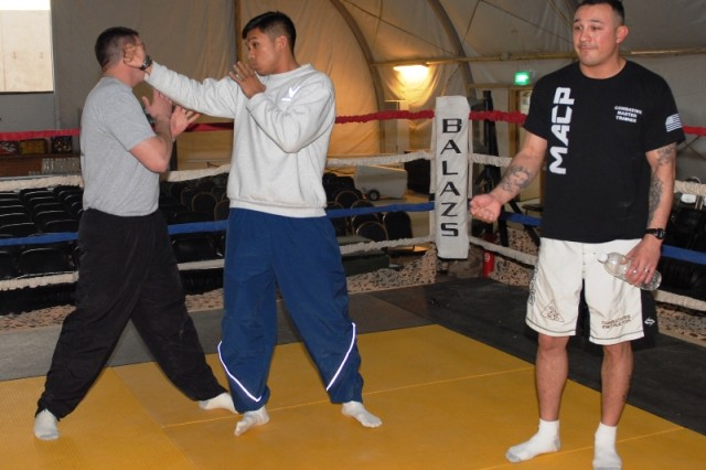 Staff Sgt. Aaron Martinez, 4th Brigade Combat Team, 1st Armored Division, (right) has Air Force Staff Sgt. Christopher Costa, 732nd Air Expeditionary Group, demonstrate a legal punch on Sgt. Francis Trunck, 4th BCT, 1st Armd. Div., at Contingency Operating Base Adder, Iraq, Jan 8, 2010.