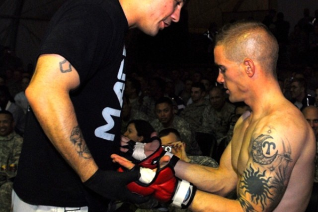 Staff Sgt. Aaron Martinez , 4th Brigade Combat Team, 1st Armored Division, checks the equipment of Sgt. James Barrett, 4th BCT, 1st Armd. Div., before he steps into the ring for his bout during Friday Night Fights on Contingency Operating Base Adder, Iraq, Jan 8, 2010.
