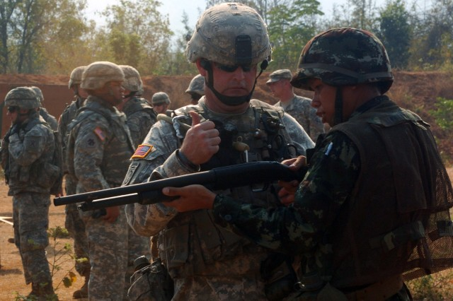 FORT SURASEE, Thailand (Feb. 3, 2010) – Sgt. Gregory Johnson, a Soldier assigned to Company C, 4th Battalion, 118th Infantry Regiment, teaches a Royal Thai Army soldier how to use a pump-action shot gun with rubber ammunition during a non-lethal weapons class at Fort Surasee, Thailand, Feb. 3. The class is part of exercise Cobra Gold 2010. CG10 marks the 29th anniversary of the annual, joint and coalition multinational exercise, hosted by the Kingdom of Thailand. The exercise consists of a Global Peacekeeping Operations Initiative Exercise, Command Post Exercise, Humanitarian Civic Assistance projects and field training exercises.  The goal of the exercise is to enhance military interoperability and improves communities through humanitarian assistance and civil action projects.