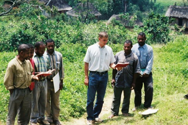 """Spc. Jon Calhoun, an X-ray technician assigned to """"C"""" Company, 203rd Brigade Support Battalion, 3rd Heavy Brigade Combat Team, 3rd Infantry Division, preaches to villagers in Kiari, New Guinea, in the spring of 2003. Calhoun, who served as a Christian missionary there for six years before re-joining the Army, helped the village by running a medical clinic."""
