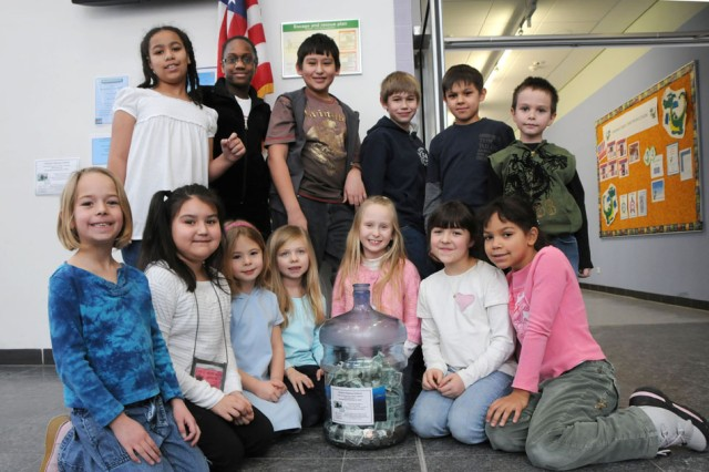 GRAFENWOEHR, Germany -- Students of Netzaberg Elementary School gather around a donation bottle holding more than $1,000. Children, parents and community members donated the money to support the relief efforts in Haiti.