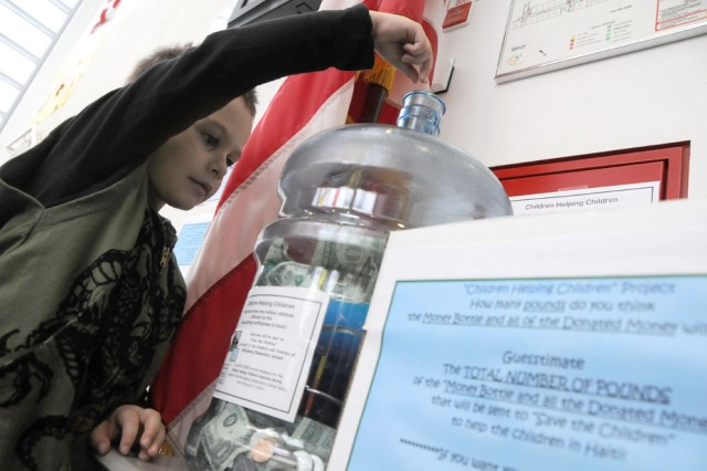 GRAFENWOEHR, Germany -- Kindergarten student Jason Garcia, 6, places a small amount of change into the donation bottle at Netzaberg Elementary School.