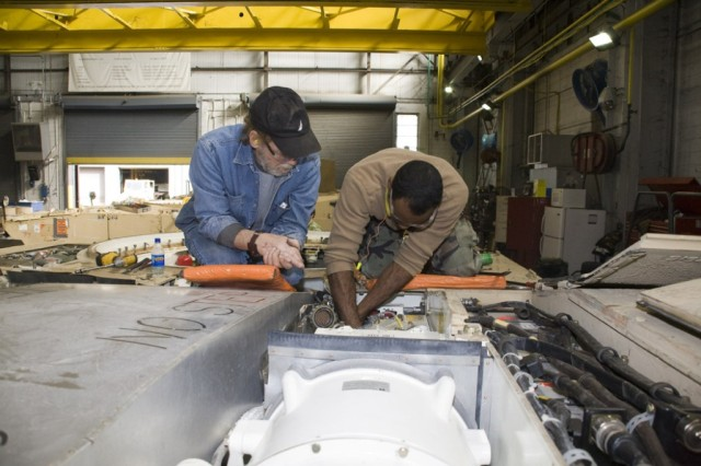 Mechanics Joe Parker (left) and Earl Wood work on electronic components in an M2A2 System Enhancement Package, version 2 in the combat disassembly/reassembly building at Anniston Army Depot.