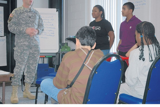 Belvoir teens Jamaisha Enoch and Izaiah Robinson stand in front of Installlation Commander Col. Jerry Blixt and Installation Command Sgt. Maj. Gabriel Berhane at the Youth Center to present issues most pressing to teens on post.