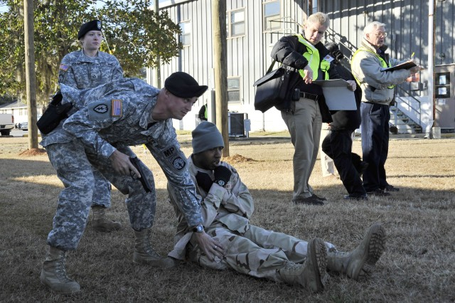 Unable to see or hear, a Soldier is assisted by a military policeman. Both are players in the Stewart Guardian exercise at Fort Stewart, Jan. 27.