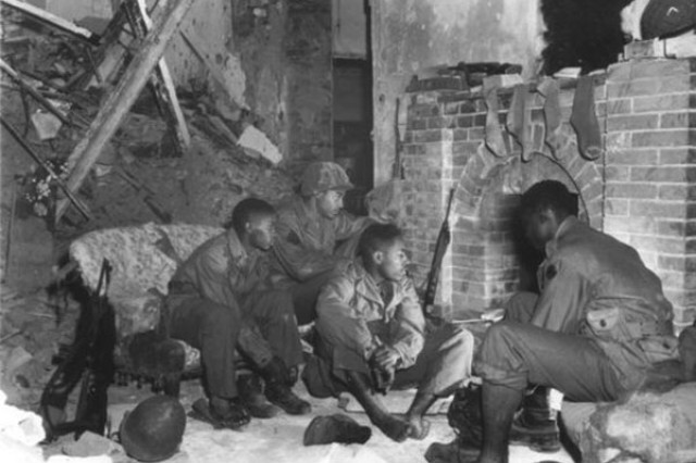 """In this file photo, Soldiers of the 92nd """"Buffalo"""" Division warm up in front of an Italian Home's fireplace during WWII."""