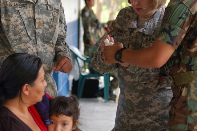 With the assistance of 1st Lt. Donny Esquival, El Salvador Army Force, U.S. Army Maj. Guerschon De Laurent, the dentist on the left assigned to the 912th Medical Detachment, and U.S. Army. Lt. Col. Marsha Shivley, with the 420th Minimal Care Detachment, provide medication dosages to a Salvadoran patient.