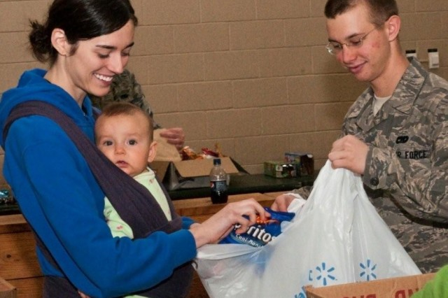 Family Readiness Leader for Headquarters and Headquarters Company, 2-407th, Meghan McCoy and her 7 - month daughter,  Stella, help package up snacks and drinks for Super Bowl themed care packages being sent to deployed Soldiers in Haiti at Green Ramp, Pope Air Force Base, Feb 3.