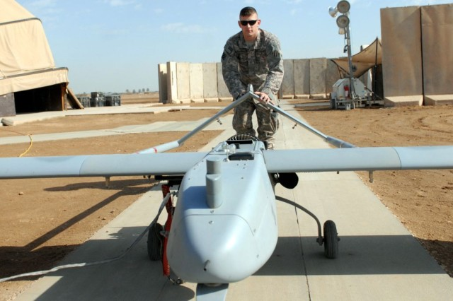 """Pfc. Anthony McCormack, a controller assigned to """"A"""" Company, Brigade Special Troops Battalion, 3rd Heavy Brigade Combat Team, 3rd Infantry Division, wheels an unmanned aerial vehicle  out to a launcher at Forward Operating Base Kalsu, Iraq, Jan. 25, 2010. The vehicle, which weighs over 300 pounds, requires three Soldiers to load it on to the launcher."""