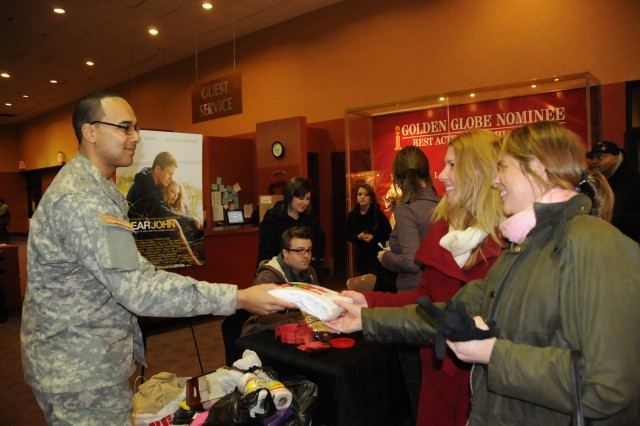 "SPC Gregory Williams receives donations for troops overseas at a February 2010 advance screening of ""Dear John."" Williams works as a movie promoter in New York."