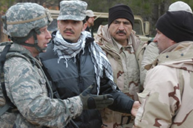 Air Force Lt. Col. Garth TerryAca,!E+(left), team leader for combat advisor class 87, explains the legal ramifications of extorting money at a check point to roleplayers during the class 87 capstone exercise Feb. 3.