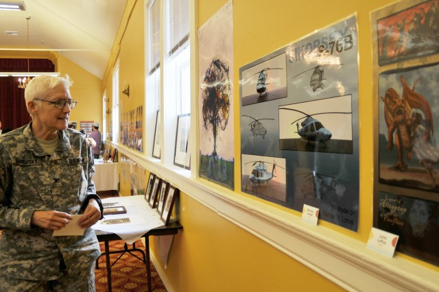 Defense Language Institute Foreign Language Center Commandant Col. Sue Ann Sandusky admires the artwork on display during the Technology Integration Division's first Art Exposition.    The exposition was a chance for the mostly incognito division to display their talents to the staff and faculty of the DLIFLC.