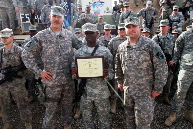 CONTINGENCY OPERATING LOCATION Q-WEST, Iraq - Pfc. Quintavis B. Byrd (center), an entry control point sentry and native of Tutwiler, Miss., holds a Command Sergeant Major award, flanked by 1st Sgt. John L. Beasley (left), a Hernando, Miss., native, and Staff Sgt. Nicholas Hughes, a native of Batesville, Miss., and Byrd's platoon sergeant, after a ceremony in the company area Feb. 1, which acknowledged Byrd for embodying the Army value of loyalty. All the Soldiers pictured serve with A Company, 2nd Battalion, 198th Combined Arms, 155th Brigade Combat Team, out of Hernando, Miss. To honor outstanding service at the end of the deployment, the senior NCOs of the battalion recognized seven Soldiers from throughout the Battalion who embody one of the Army values of loyalty, duty, respect, service, honor, integrity and personal courage.
