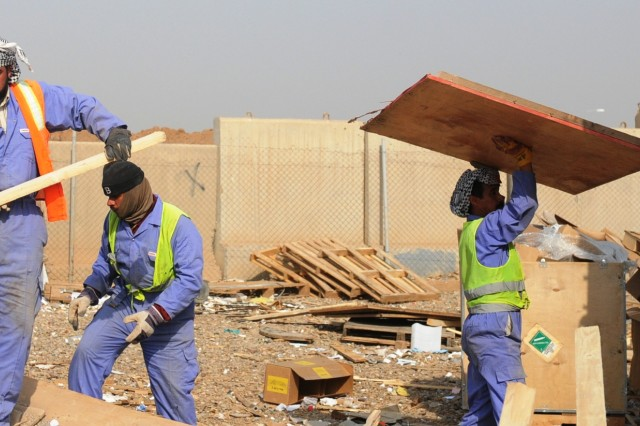 Iraqi workers, contracted by the United Mandour Company, load wood onto a truck Feb. 1 at the recycling yard at Joint Base Balad, Iraq. The pallets will be resold or reused in nearby villages. The jobs and supplies help boost the local economy and further the partnership between U.S. forces and the Iraqi people.