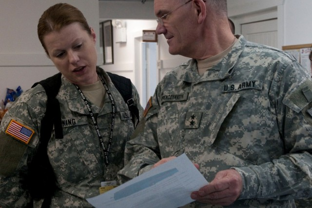 Warrant Officer Kerry King, Mandan, N.D., shows Maj. Gen. David A. Sprynczynatyk, adjutant general, North Dakota National Guard, some paperwork during a recent visit to Camp Bondsteel, Kosovo.  Sprynczynatyk came to Camp Bondsteel to show support of Soldiers from N.D. who are deployed on a NATO peacekeeping mission there.