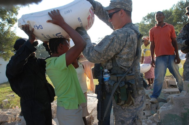 Pfc. Blake Parsons, a native of Dallas, Texas and a forward observer with Headquarters and Headquarters Company, 2nd Brigade Combat Team, 82nd Airborne Division helps a Haitian woman balance a bag of rice on her head at a World Food Program distribution site in Port-au-Prince on Feb. 6. Paratroopers with HHC, 2BCT helped Jordanian United Nations soldiers secure the site. (U.S. Army photo by Pfc. Kissta M. Feldner, 2BCT, 82nd Abn. Div. PAO)