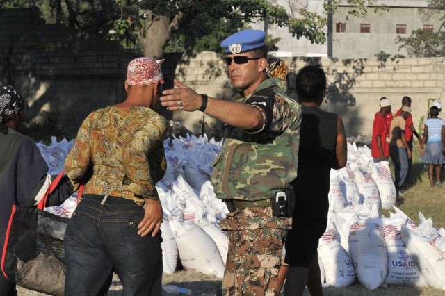 A Jordanian United Nations military police officer directs Haitian citizens collecting bags of rice at a World Food Program distribution point in Port-au-Prince, Haiti on Feb. 6. Paratroopers assigned to Headquarters and Headquarters Company, 2nd Brigade Combat Team, 82nd Airborne Division assisted the U.N. with security during the drop. (U.S. Army photo by Pfc. Kissta M. Feldner, 2BCT, 82nd Abn. Div. PAO)