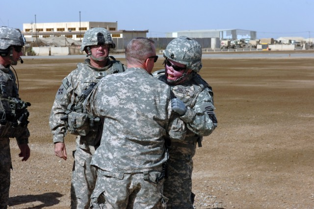 CAMP TAJI, Iraq - Command Sgt. Maj. Lawrence Wilson (left), from Austin, Texas, the command sergeant major of U.S. Forces-Iraq, watches as Sgt. 1st Class Michael Schlitz (right) gives a farewell embrace to Col. Douglas Gabram (center), from Cleveland, Ohio, commander, 1st Air Cavalry Brigade, 1st Cavalry Division, U.S. Division-Center, Feb. 4. Schlitz and seven other wounded warriors visited 1st ACB as part of Operation Proper Exit, which was the program's third visit to the Air Cav.