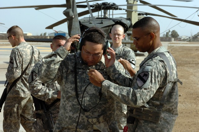 CAMP TAJI, Iraq - While adjusting the mouthpiece, Lt. Col. Charles Dalcourt (right), of Baton Rouge, La., commander, 1st Battalion, 227th Aviation Regiment, 1st Air Cavalry Brigade, 1st Cavalry Division, U.S. Division-Center, shows Cpl. Charles Dominguez, from Ontario, Calif., how to operate a crew chief headset Feb 4. Dominguez, who was visiting 1st ACB as part of Operation Proper Exit, suffered serious burns in 2006 when he was attacked by a suicide bomber while supporting the ongoing war on terror in Iraq.
