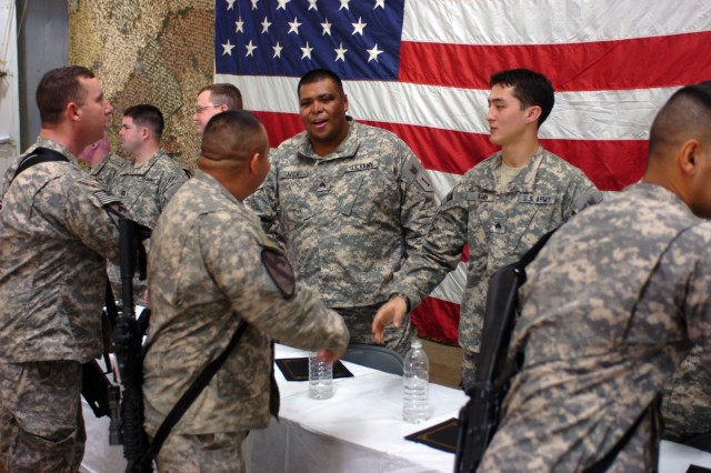 CAMP TAJI, Iraq - Soldiers from 1st Air Cavalry Brigade, 1st Cavalry Division, U.S. Division-Center, shake hands with wounded warriors who were visiting as part of Operation Proper Exit, a program designed to bring wounded veterans back to the places they were injured. Two of the wounded warriors, Sgt. Omar Avila (center), from Brownsville, Texas, and Sgt. Jay Fain (right), from Columbia, S.C., finish talking with 1st ACB Soldiers following a town hall meeting Feb. 4. The wounded veterans talked about never giving up or quitting - values held dear to the Army.