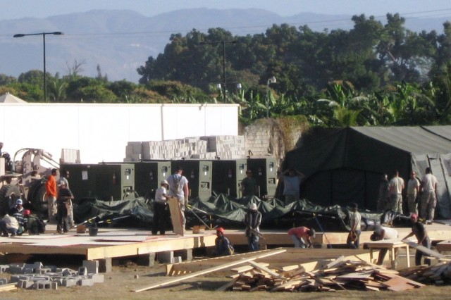Members of the U.S. Army South Humanitarian Assistance Survey Team construct the deployable Joint Command and Control Center, the headquarters for Joint Task Force-Haiti. The Army South team worked together with both governmental and non-governmental organizations, such as the U.S. Army Corps of Engineers, USAID and Haitian workers, to complete the command center.