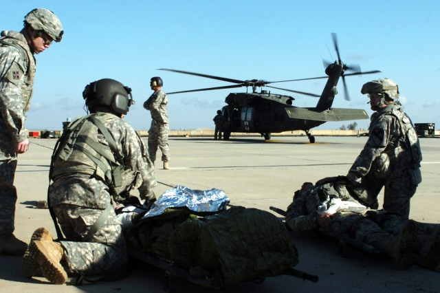 CAMP TAJI, Iraq-A UH-60 Black Hawk medevac helicopter waits in the distance as medics from 1st Air Cavalry Brigade, 1st Cavalry Division, U.S. Division-Center, prepare to load patients from a mass casualty exercise onto the aircraft at the Forward Arming and Refueling Point Feb. 5