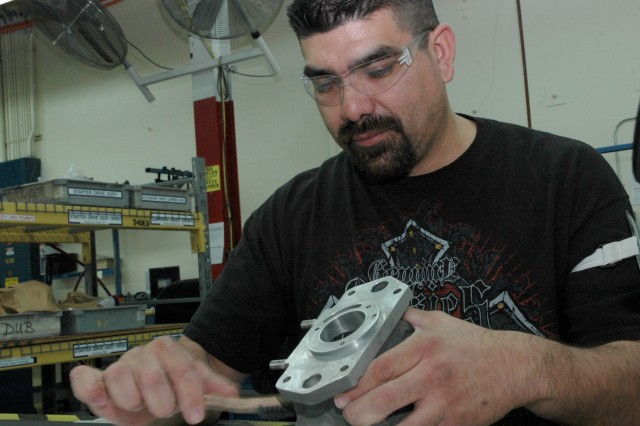 Power Train Aircraft Mechanic Luis Olivo cleans a starter assembly unit for the CH-47 Chinook helicopter. Graduating two years ago from the Student Career Experience program, Luis recommends the program to anyone wanting to begin a good career.
