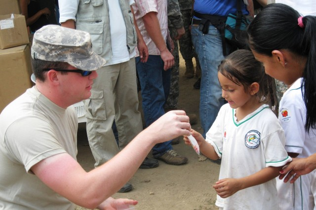 Pfc. Bryan Baker, assigned to the 425th Minimal Care Detachment out of Indianapolis, Ind., hands out vitamins to a young Colombian patient. (U.S. Army photo by 2nd Lt. Bill Hooks, 425th Minimal Care Detachment/RELEASED)