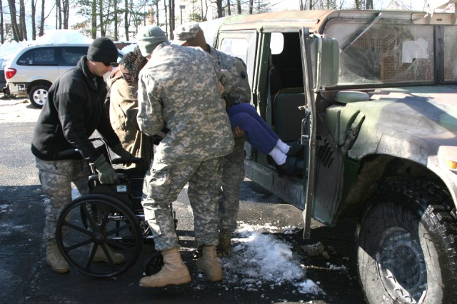 Soldiers from the Norfolk-based Company G, 429th Brigade Support Battalion, 116th Brigade Combat Team assist Fairfax County, Va. resident Olive Lewis out of their Humvee for medical transport Feb. 8. Lewis was not able to make a needed medical appointment for kidney dialysis, so the Fairfax County Emergency Operations Center dispatched the Virginia National Guard was called to transport her.