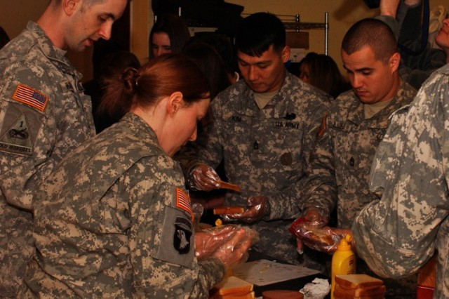 From left: Sgts. 1st Class Kevin Hartman, Mary Mittlesteadt, Kap Kim, Alex Licea and David Wheeler work a sandwich-making assembly line during their class community project where they volunteered for the charitable organization Happy Helpers for the Homeless.
