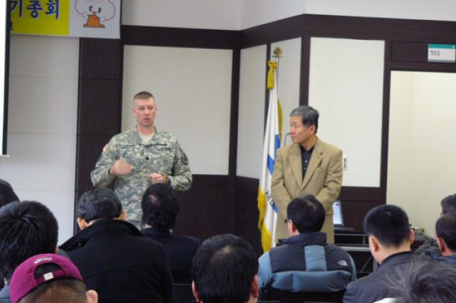 (From left standing) Lt. Col. Richard Fromm, USAG-Casey commander, addresses the KSTA business men gathered in the Dongducheon Saemaeul Geumgo Building in South Korea, as Pae, Tong su translates, to discuss issues and concerns regarding entertainment and commerce between U.S. personnel and Korean shop owners Feb. 4. - Courtesy photo