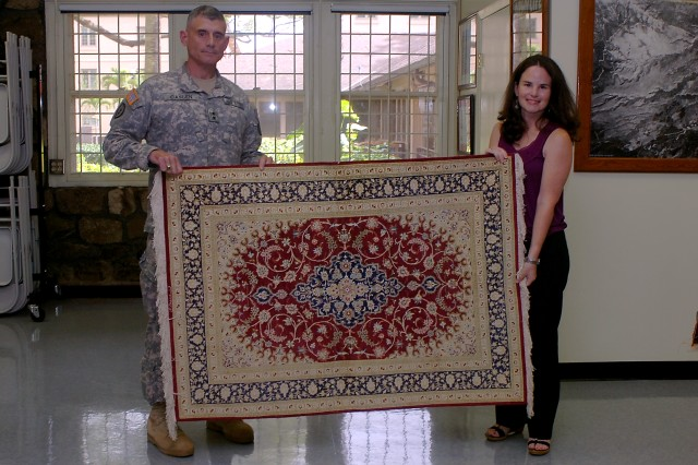Maj. Gen. Robert L. Caslen Jr., commanding general, 25th Infantry Division, and Kathleen Ramsden, Tropic Lightning Museum Curator, display a silk rug, one of the donations presented to the Tropic Lightning Museum, Feb. 4. The rug was one of several gifts given to the 25th Inf. Div. by its Iraqi partners during its most recent deployment to northern Iraq. (U.S. Army photo by Spc. Mahlet Tesfaye, 25th Infantry Division Public Affairs Office)
