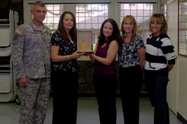 Maj. Gen. Robert L. Caslen Jr., commanding general, 25th Infantry Division, and his wife, Shelly Caslen (second from left), donate a gold jewelry set to Kathleen Ramsden (middle), the Tropic Lightning museum curator, with other Task Force Lightning spouses, Feb. 4. (U.S. Army photo by Spc. Mahlet Tesfaye, 25th Infantry Division Public Affairs Office).
