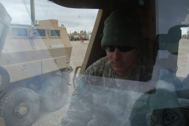 CONTINGENCY OPERATING LOCATION Q-WEST, Iraq - Seen through the clean windshield of his Min-Resistant, Ambush-Protected gun truck, Sgt. Edwin L. Pauley, a scout truck commander from Salisbury, Md., inspects the truck's communication system in the company motor pool here Feb. 4.  The windows stay cleaner during missions because Pauley's driver, Spc. Michael A. Boucher, a scout truck driver from Batesville, Miss., made additional mud flaps for the Self-Protection Adaptive Roller Kit - attached to the front of the vehicle, absorbing bomb damage and shielding the vehicle and crew, said Pauley. Both men serve with 1st Platoon, B Company, 2nd Battalion, 198th Combined Arms, 155th Brigade Combat Team, out of Greenwood, Miss.