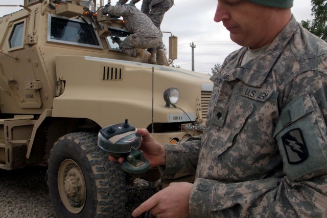 CONTINGENCY OPERATING LOCATION Q-WEST, Iraq - Spc. Michael A. Boucher, a scout truck driver from Batesville, Miss., holds a remote control switch he rigged to operate a spotlight he installed in the gun turret of his Mine-Resistant, Ambush-Protected gun truck, in the company motor pool. Feb. 4. Boucher also made additional mud flaps for the Self-Protection Adaptive Roller Kit - attached to the front of the vehicle, absorbing bomb damage and shielding the vehicle and crew - and those flaps have decreased mud splatter to windows and crew. Boucher serves with 1st Platoon, B Company, 2nd Battalion, 198th Combined Arms, 155th Brigade Combat Team, out of Greenwood, Miss.