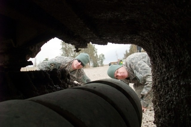 CONTINGENCY OPERATING LOCATION Q-WEST, Iraq - Sgt. Edwin L. Pauley (left), a scout truck commander from Salisbury, Md., and Spc. Michael A. Boucher, a scout truck driver from Batesville, Miss., examine the road mud caked beneath the mud flaps of the Self-Protection Adaptive Roller Kit in their company motor pool here Feb. 4.  Boucher made additional mud flaps for the SPARKs - which is attached to the front of the vehicle, absorbing bomb damage and shielding the vehicle and crew - and those flaps have significantly increasing the safety, security and efficiency of his scout truck, said Pauley. Both men serve with 1st Platoon, B Company, 2nd Battalion, 198th Combined Arms, 155th Brigade Combat Team, out of Greenwood, Miss.