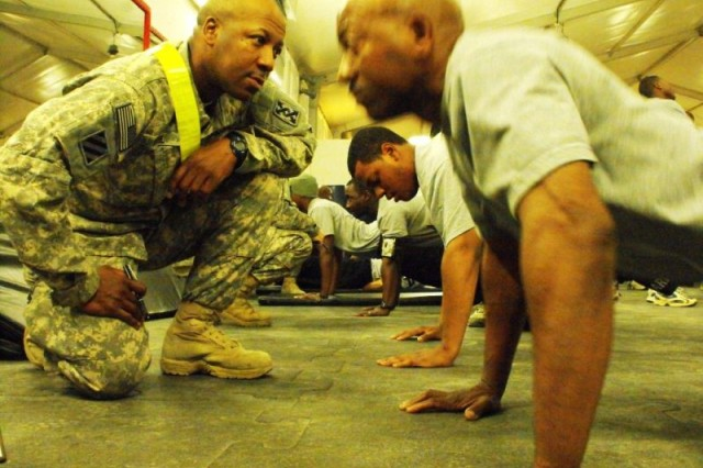CAMP LIBERTY, Iraq-Staff Sgt. Frederick McNeil, of Liberty, Miss., grades Staff Sgt. Larry Walker from Palm Harbor, Fla., during the push-up event of the army physical fitness test.  This is the first test given while in theater for the 296th Transportation Company, 260th Sustainment Support Battalion, 15th Sustainment Brigade, 13th Sustainment Command (Expeditionary). Frederick is a heavy equipment transport operator and Walker is the communications noncommissioned officer in charge.